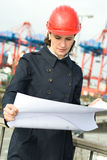 Female Engineer. Female civil engineer wearing helm and checking the drawings in front of container terminal in harbour stock photos