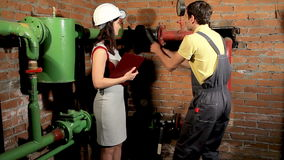 Female engineer asks the employee to open the valve. Male worker opens ball valves. stock video footage