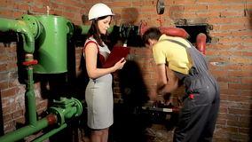 Female engineer asks the worker to close the valves. Male worker close ball valves. stock video