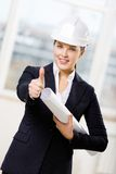Female engineer with blueprint thumbs up. Wearing white hand hat female engineer with blueprint thumbs up Royalty Free Stock Images