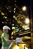 Female engineer with blueprints on factory Royalty Free Stock Photos