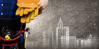 Female engineer. Bottom view of woman engineer with tool belt on waist Royalty Free Stock Photo
