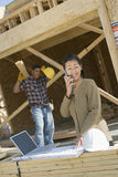 Female Engineer On Call With Worker At Site Stock Photos