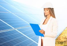 Female engineer developing project on installation of  panels outdoors. Female engineer developing project on installation of solar panels outdoors Royalty Free Stock Photography