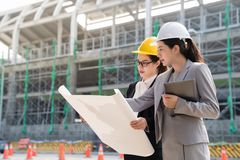 Female engineer displaying a building plan. A female engineer displaying a building plan to another women architect. They both wearing a yellow hard helmet.On a royalty free stock photos