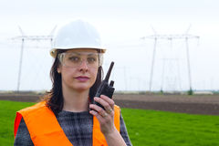 Female engineer electrician. Supervising female engineer for electrification using walkie- talkies near the transmission line Royalty Free Stock Photo