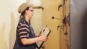 A female engineer going to the electrical panel and records the readings of devices in the switchboard. The average plan stock video footage