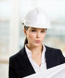 Female engineer in hard hat hands blueprint. Female engineer in white hard hat hands blueprint. Concept of successful construction Royalty Free Stock Image