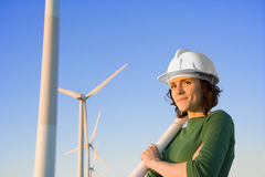 Female Engineer Holding Blueprints in Front of Modern Wind Turbi Stock Images