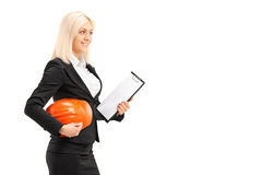 Female engineer holding a helmet and a clipboard Royalty Free Stock Photography