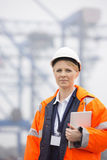 Female engineer holding tablet PC in shipping yard Royalty Free Stock Photos
