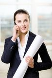 Female engineer with layout speaks on phone. Female engineer keeping layout speaks on cell phone Royalty Free Stock Image
