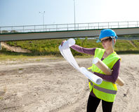 Female engineer looking at blueprints. In construction site Stock Photos