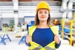 Female engineer making super hero gesture. Young female engineer making powerful super hero gesture by pulling vest as professional wonder woman concept on stock photography