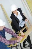 Female engineer and male builder wearing helmets inside bulding royalty free stock photo