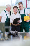 Female engineer and manufacturing labourers Royalty Free Stock Photography