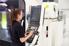 Female Engineer Operating CNC Machinery On Factory Floor Royalty Free Stock Photo