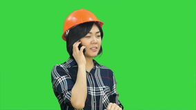 Female engineer with orange helmet having a phone call via smartphone on a Green Screen, Chroma Key stock footage