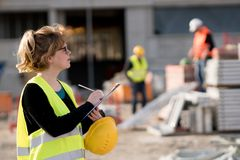 Female engineer posing. Young female civli engineer at work on construction site royalty free stock images