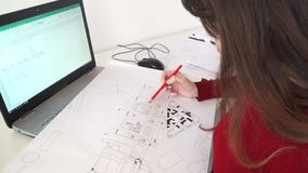Female engineer sits at the desk in her office, types on a laptop, blueprints laying on her desk