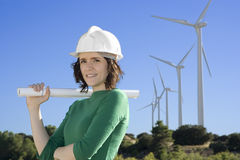 Female engineer stands in front of windmills Royalty Free Stock Photography