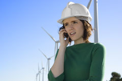 Female Engineer Talking on Cell Phone in Front of Modern Wind Tu Stock Photo