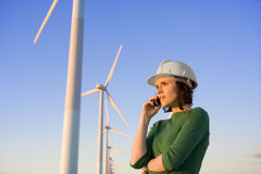 Female Engineer Talking on Cell Phone in Front of Modern Wind Tu Stock Image
