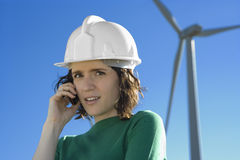 Female Engineer Talking on Cell Phone in Front of Modern Wind Tu Stock Images