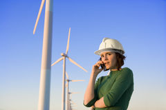 Female Engineer Talking on Cell Phone in Front of Modern Wind Tu Royalty Free Stock Photography