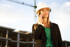 Female Engineer Talking on Phone Standing in Front of Constructi Royalty Free Stock Photos