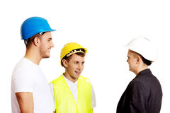 Female engineer talking with two builders royalty free stock photography