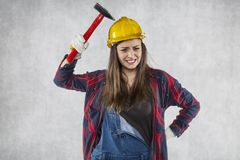A female engineer is testing the strength of a helmet with a smi Stock Photo