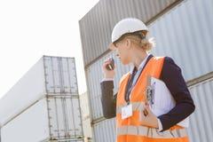Female engineer using walkie-talkie in shipping yard Stock Photo