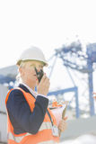 Female engineer using walkie-talkie in shipping yard Stock Photography