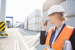 Female engineer using walkie-talkie in shipping yard Stock Image