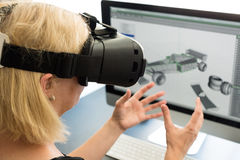 Female engineer with VR glasses. Female engineer working on computer creating a racecar using VR virtual reality glasses. Concept for woman in hightech jobs Royalty Free Stock Photography
