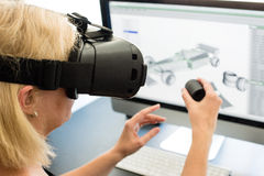 Female engineer with VR glasses. Female engineer working on computer creating a racecar using VR virtual reality glasses and controller. Concept for woman in Stock Image