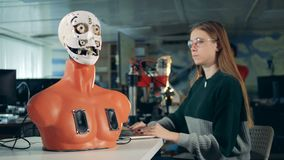 A woman looks at working robot, close up. stock video footage