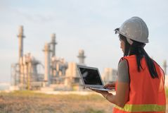 Female engineer is wearing a hard hat on a digital tablet with a power plant.  royalty free stock photos