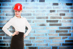 Female engineer woman architect in red safety helmet and brick wall Royalty Free Stock Photography