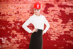 Female engineer woman architect in red safety helmet and red wall Royalty Free Stock Photography