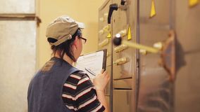 A female engineer writes down the readings of electrical appliances in the switchboard. The average plan stock video