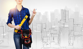 Female engineer. Young pretty woman engineer with tool belt on waist Stock Photos