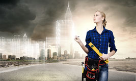 Female engineer. Young pretty woman engineer with tool belt on waist Stock Image