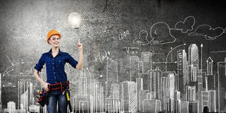 Female engineer. Young pretty woman engineer with tool belt on waist Royalty Free Stock Images