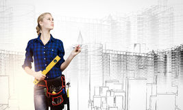 Female engineer. Young pretty woman engineer with tool belt on waist Stock Images