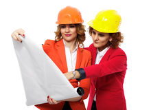 Female engineers in hardhats looking over project Stock Images
