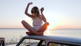 Female enjoy good music at sunset on automobile at background nature in slow motion, young woman sitting at roof car