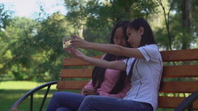 Female enjoy meeting at saturday morning. Two asian young girls take a selfie photo on the mobile phone. Happy women sitting on the bench in the park. attractive stock video