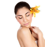 Female enjoying day spa. Image of sensual brunette girl with fresh yellow lily flower in head isolated on white background, closeup portrait of gorgeous woman Stock Photos